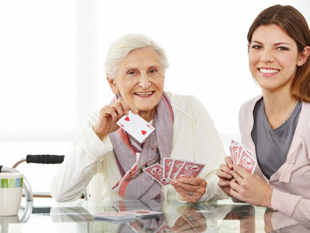 stock-photo-young-eldercare-nurse-playing-cards-with-happy-senior-woman-172192568